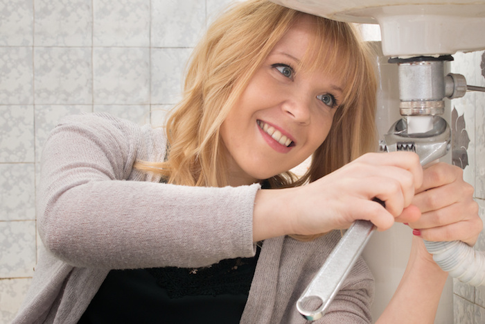 A woman trying her hand at DIY plumbing