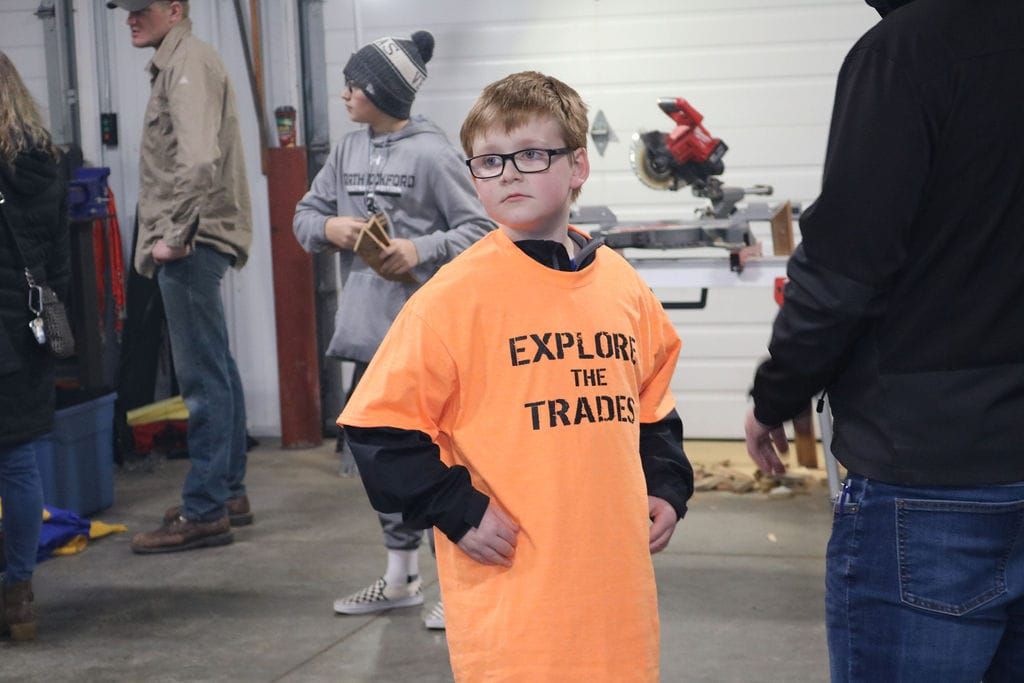 A young Rockford kid wearing an orange tee at Kellermeier's skilled trades night.