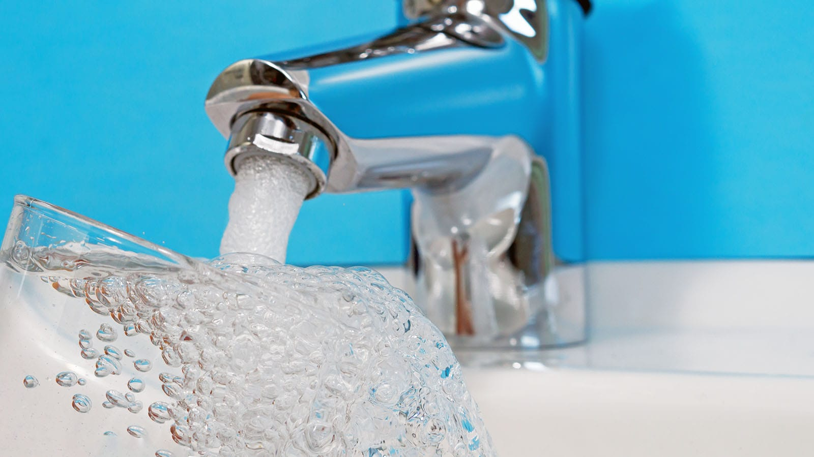 A water faucet overflowing a glass with clean drinking water. Backflow testing services ensure the water is clean every time.