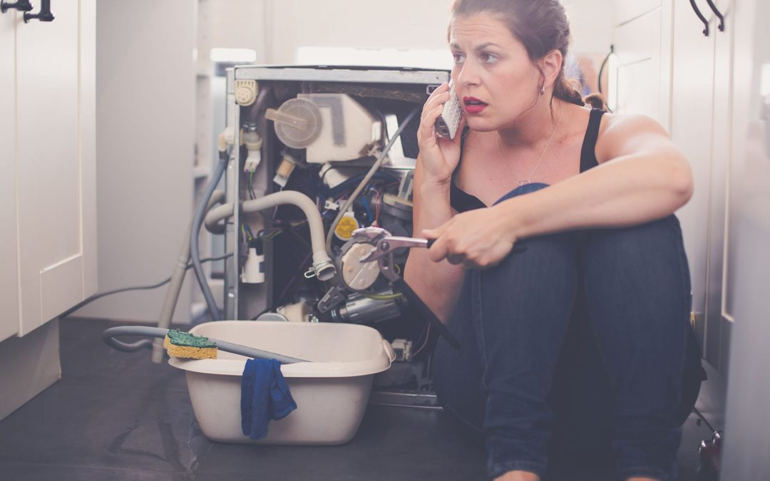 A woman holding a wrench deals with a plumbing emergency by calling a plumber.