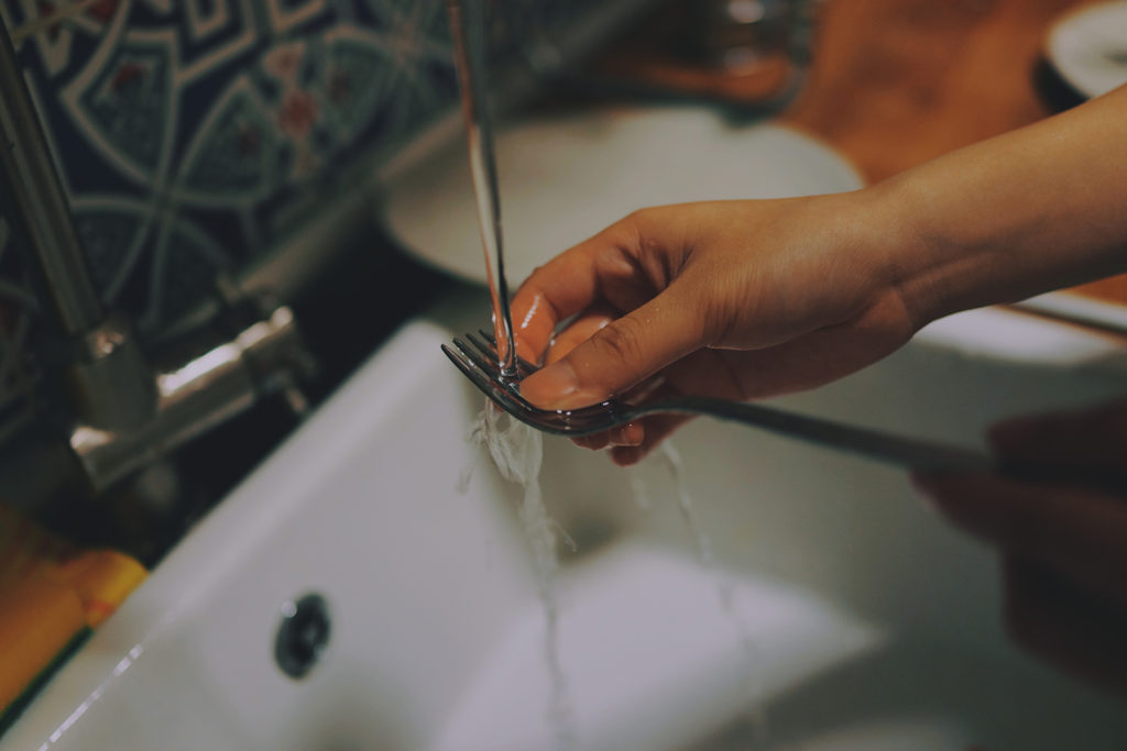 A woman washes a fork in the sink. A broken dishwasher isn't one of the big plumbing woes you think it is.