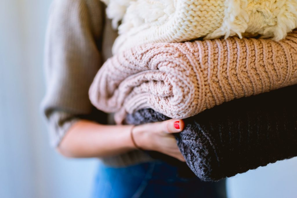 A woman holds folded towels fresh out of thew washing machine