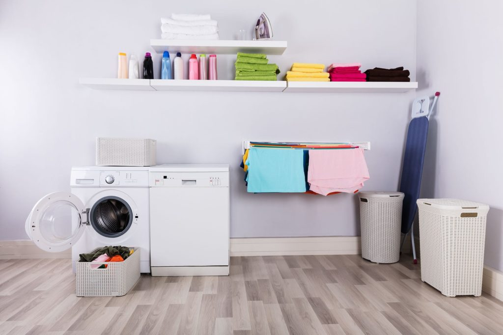 A laundry room with a washer and dryer, folded clothes, and a hamper. Laundry room plumbing is responsible for more than washer connections.