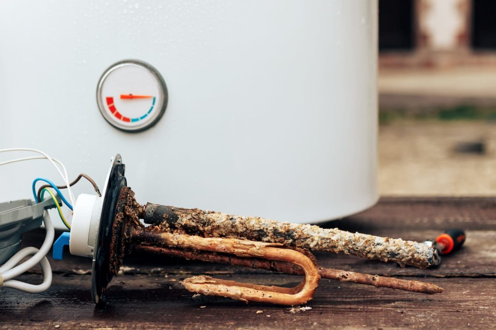 Old appliances can create water heater sounds signaling trouble. A rusted and scaling heater implement.