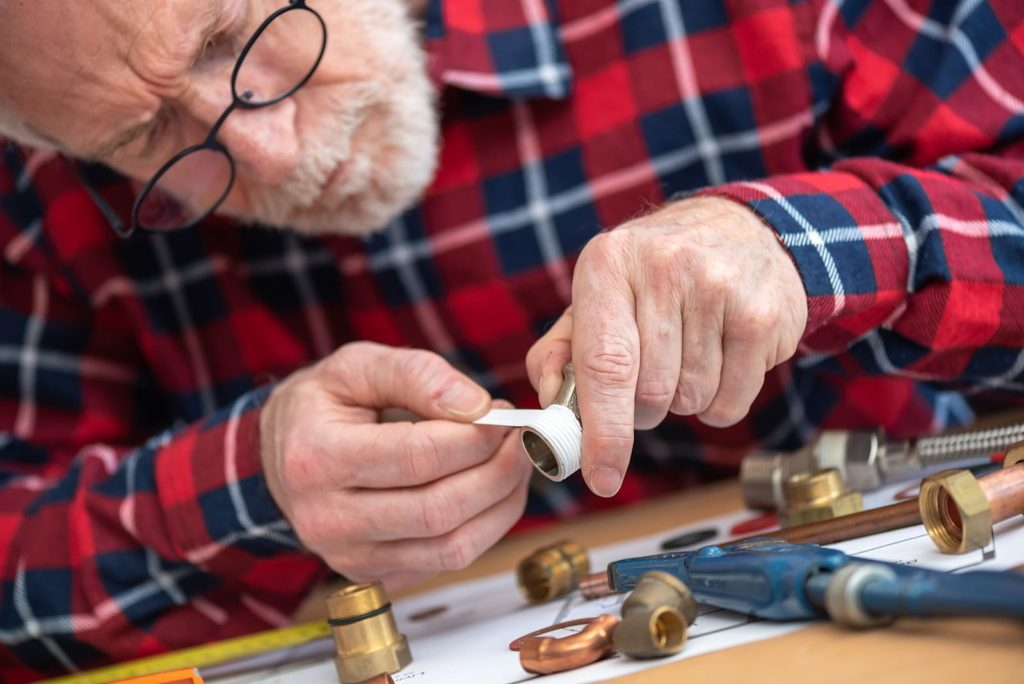 An older man is learning how to use plumbers tape.