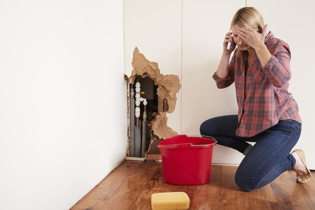 A pipe burst inside a wall that has born torn apart. A woman kneeling next to it is calling for a plumber.