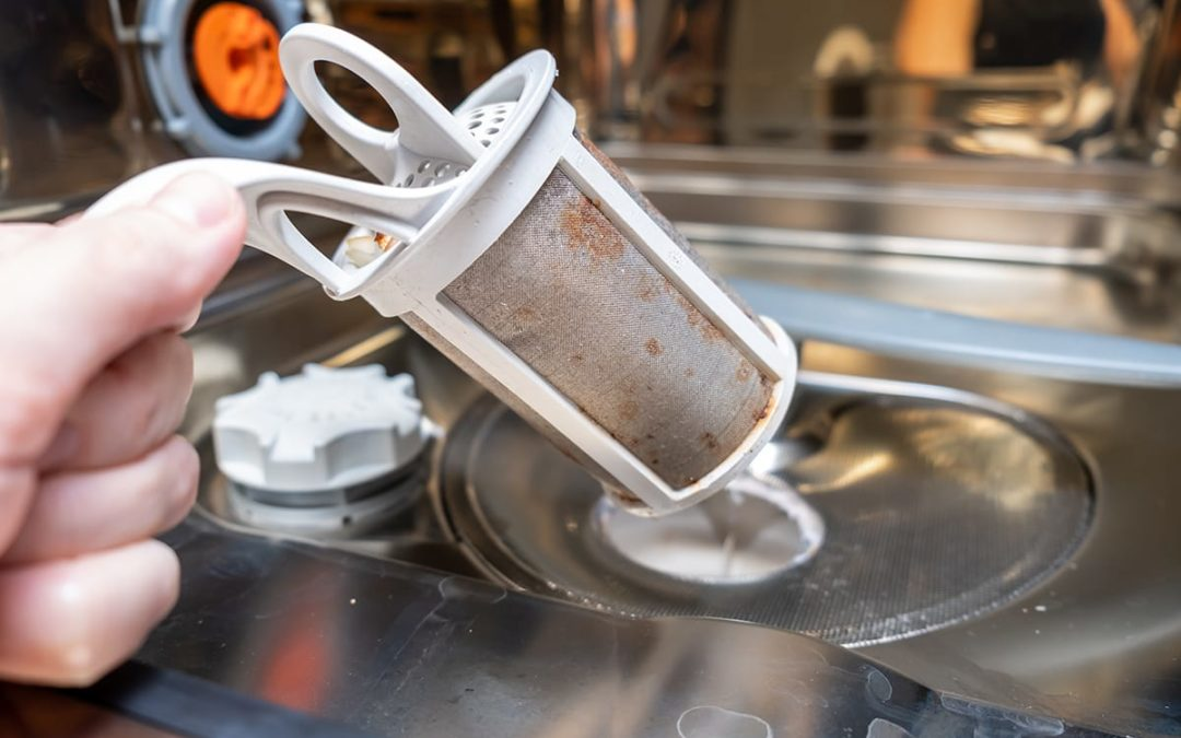 Learn how to clean a dirty dishwasher with Kellermeier Plumbing. A woman removes the catch trap of a dirty dishwasher.