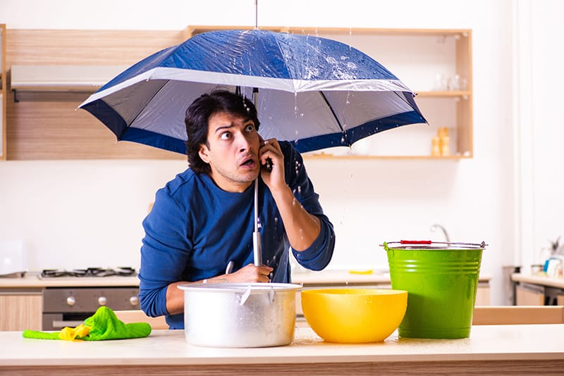 Household plumbing problems can build up over time. A man holds an umbrella while water drips from his ceiling.